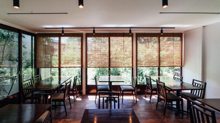 """""""茶房 空花""""のメインダイニング。大きな窓の外には美しいお庭と時折とおり過ぎていく江ノ電が"""